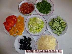 Пока тесто подходит готовим начинку для пиццы. Листья петрушки мелко порезать, помидоры разрезать пополам, лук порей порезать колечками, перцы порезать кольцами, огурец нарезать на половинки, маслины разрезать пополам, сыр натереть на крупной терке.
