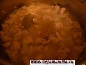 Смешать лук с филе курицы в кастрюле для тушения. Долить кипяченой теплой воды, чтобы она покрывала мясо. Довести до кипения. Добавить лавровый лист. Тушить на медленном огне в течение 20-25 минут.