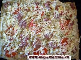 Сыр натереть на крупной или средней терке. Из духовки достать пиццу и посыпать сыром.