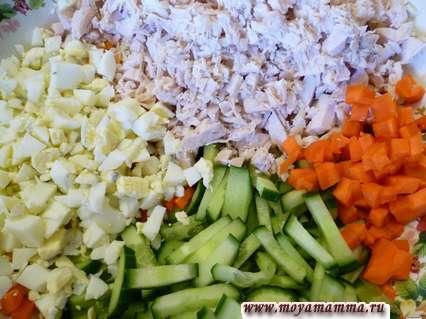 Филе курицы мелко порезать, огурец порезать узкими полосками, морковь порезать небольшими кубиками, яйца порезать небольшими кусочками.