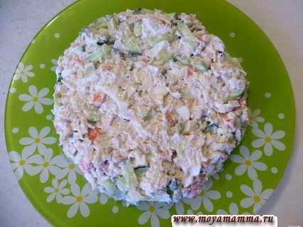 Выкладываем салат на плоскую тарелку и формируем одновременно круглую форму, слегка уплотняем при помощи ложки.