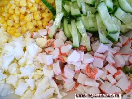 Подготовить ингредиенты для салата - крабовые палочки порезать кубиками, огурец порезать узкими полосками, яйца - небольшими кубиками. Все смешать вместе со сладкой кукурузой.