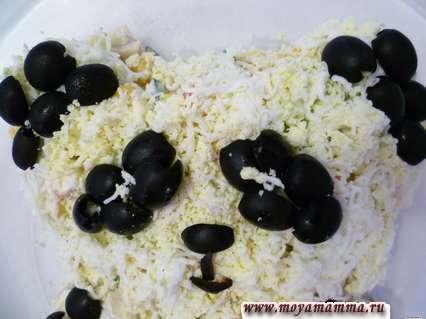 Маслины разрезать вдоль. Оформляем ушки панды - закрываем их половинками маслин.Оформляем глазки. на каждый глаз у нас ушло 5 половинок маслин. В центре глаза немного тертого яйца. Оформляем носик с ротиком. Здесь необходимо вырезать полоски из маслин так как показано на фото.