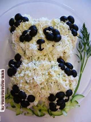 """Свежие огурцы порезанные узкими полосками разложить под лапками панды. Веточку укропа в качестве """"бамбука"""" уложить сбоку от панды. Красивый и простой салат для детей готов."""