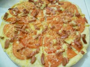 Пицца из дрожжевого теста с помидорами, жареной колбасой, сыром