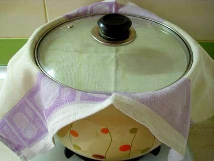 Верх кастрюли прикрыть полотенцем, установить сверху крышку.