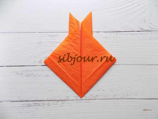 Сгиб симметрично с левой стороны оранжевой бумажной салфетки